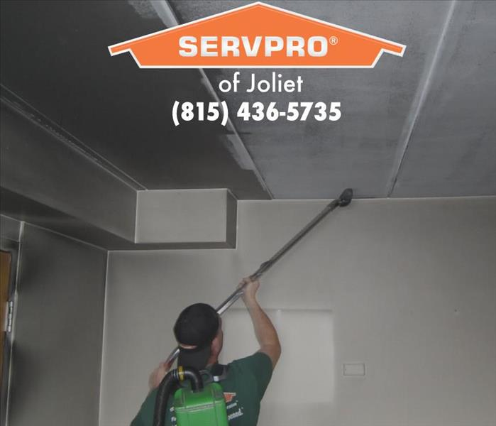 Team member cleaning wall and ceiling.